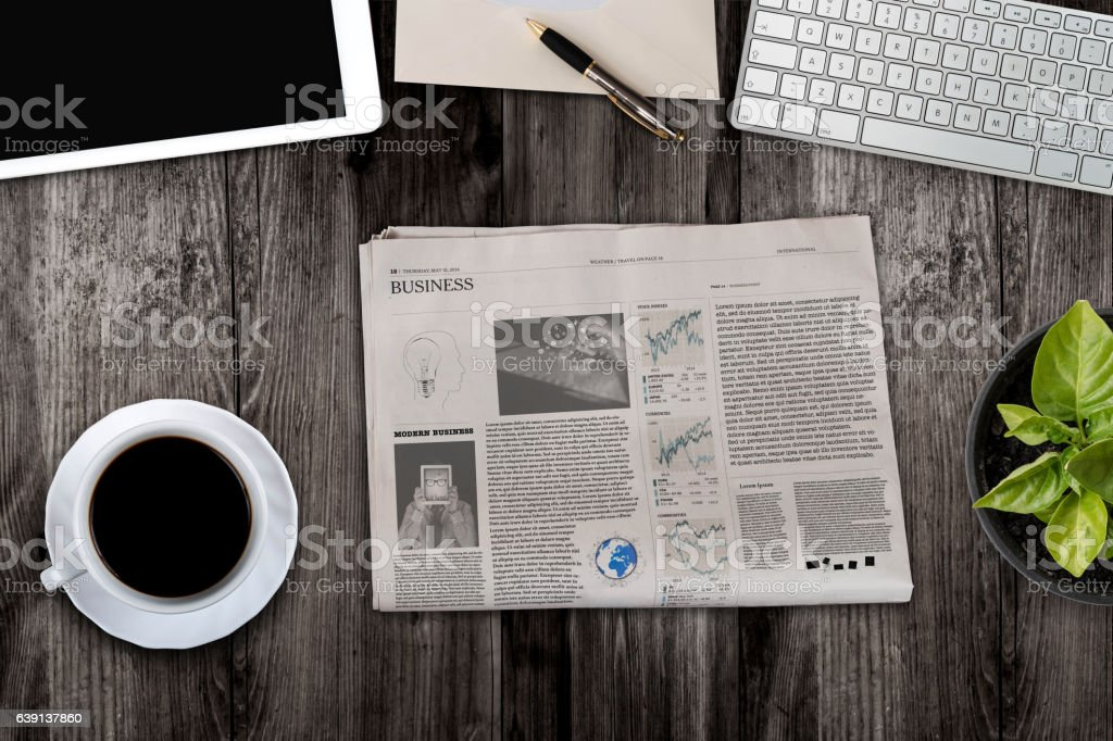 Daily newspaper and tablet pc on the wooden table. stock photo