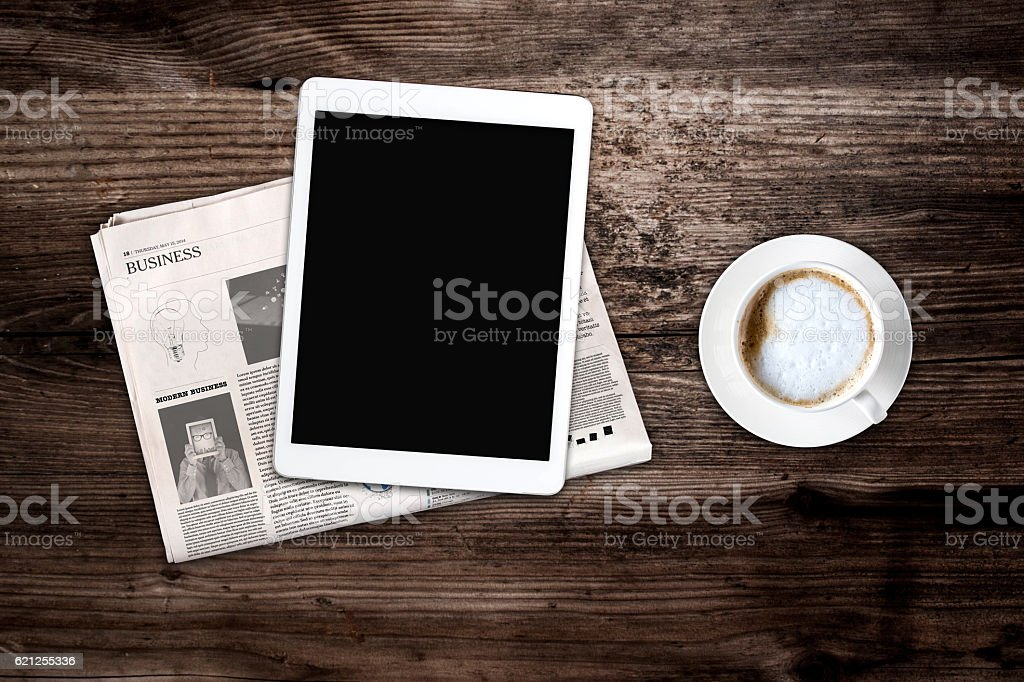 Daily newspaper, coffee and tablet with a blank screen.