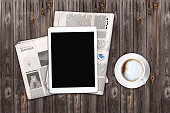 Daily newspaper and tablet with a blank screen on the wooden table. Above view. Text generated Lorem ipsum.