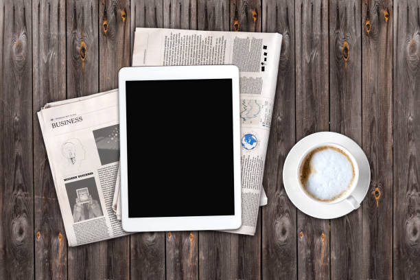 Daily newspaper, coffee and tablet with a blank screen. Daily newspaper and tablet with a blank screen on the wooden table. Above view. Text generated Lorem ipsum. article stock pictures, royalty-free photos & images