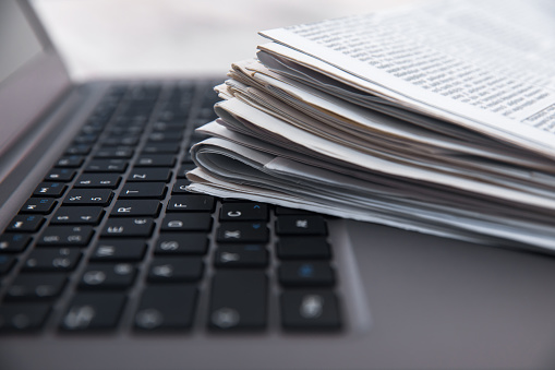 Pile of daily papers with news on the computer