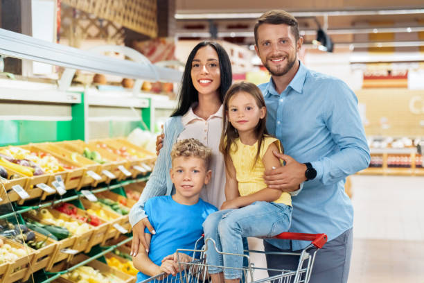 Daily Shopping. Family of four in the supermarket with cart standing near vegetables posing to camera happy stock photo