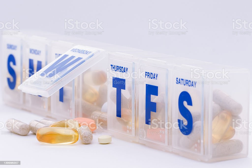 Daily vitamin and supplement pills with organizer stock photo