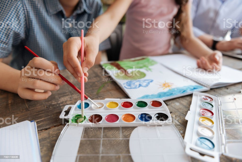 Dainty hands of children picking colors stock photo