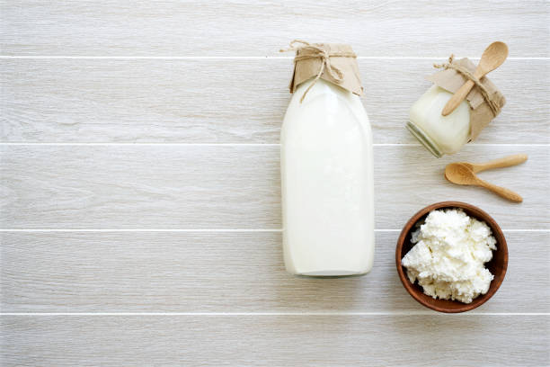 productos lácteos en frascos de vidrio en fondo claro - kéfir fotografías e imágenes de stock