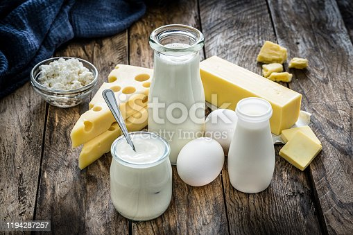 High angle view of most common dairy products shot on rustic wooden table. The composition includes milk, sour cream, butter, yogurt, eggs and cottage cheese. Predominant colors are white, yellow and brown. High resolution 42Mp studio digital capture taken with Sony A7rii and Sony FE 90mm f2.8 macro G OSS lens