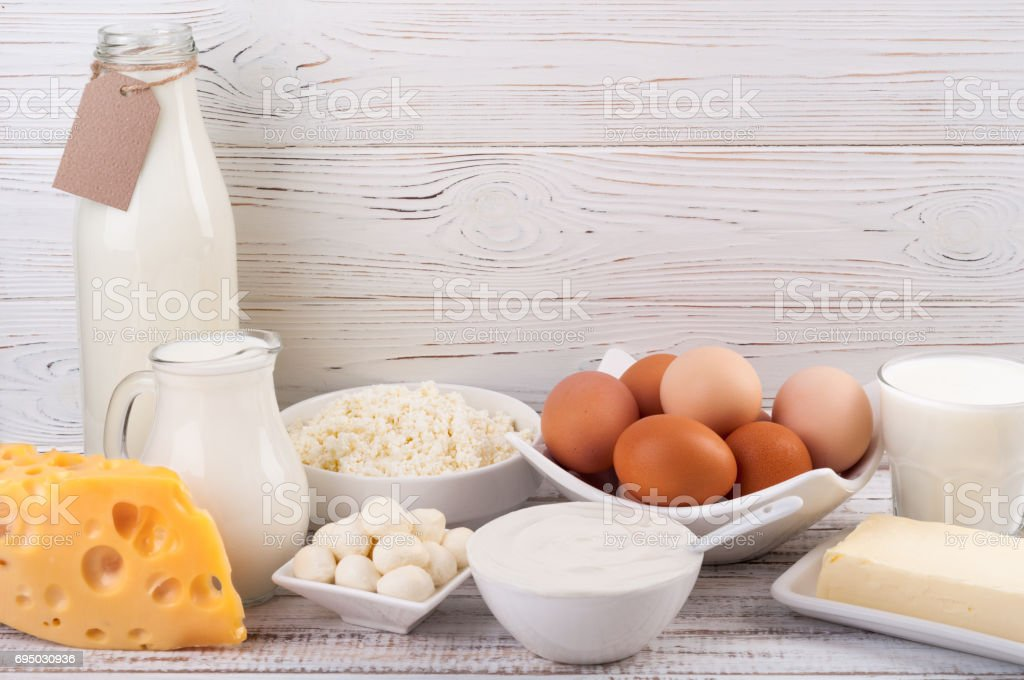 Dairy products on wooden table. Milk, sour cream, cheese, egg, yogurt...