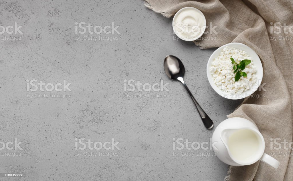 Various dairy products on grey background, top view, copy space