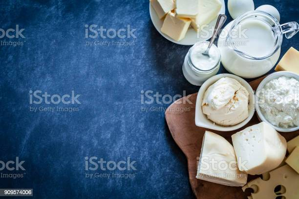Top view of dairy products assortment shot on bluish tint kitchen table. The composition is at the right of an horizontal frame leaving useful copy space for text and/or logo. Dairy products included are milk, yogurt, butter, mozzarella, mascarpone, emmental cheese, ricotta, eggs and goat cheese. DSRL studio photo taken with Canon EOS 5D Mk II and Canon EF 100mm f/2.8L Macro IS USM