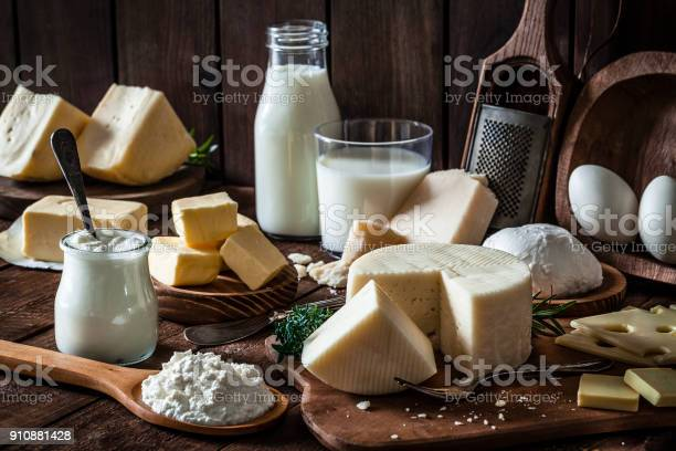 Dairy products assortment shot on rustic wooden table. Dairy products included are milk, yogurt, butter, goat cheese, mozzarella, ricotta, Parmesan cheese, emmental cheese, eggs and hard cheese. Low key DSRL studio photo taken with Canon EOS 5D Mk II and Canon EF 100mm f/2.8L Macro IS USM