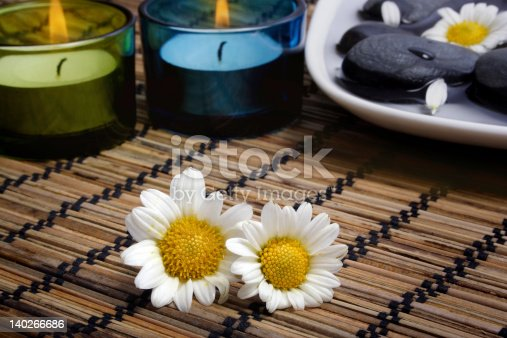1175869940 istock photo Daisies before black pebbles and candles 140266686