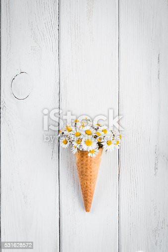 daisy flowers in the ice cream cone on white wooden background