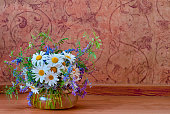 A bouquet of wild summer field flowers of chamomile and mouse peas in a glass vase on a wooden floor and a brown white background.