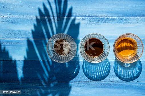 Dalgona coffee on shadow of palm tree background