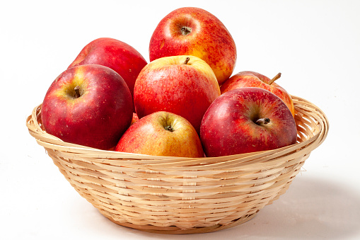 Dali apples in a basket on a white background