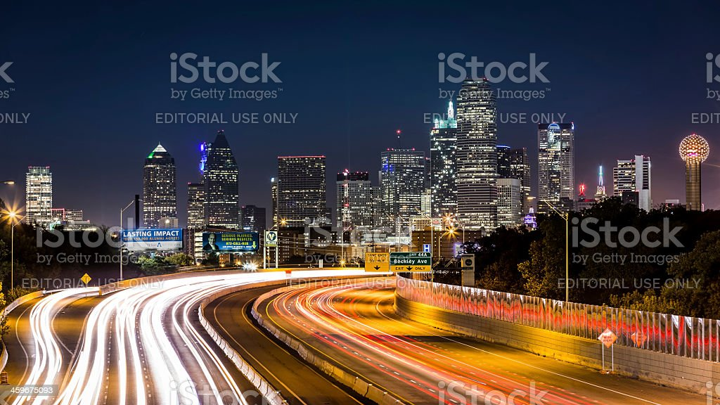 Dallas skyline by night. The rush hour traffic leaves light trails on...