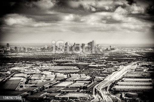 The distant downtown skyline of beautiful Dallas, Texas in black and white and toned for a retro feel in sepia.