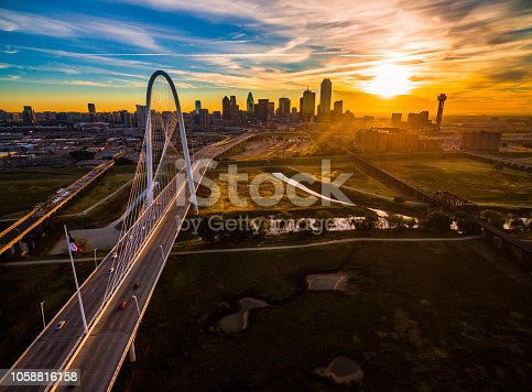 Aerial drone view high above Dallas , Texas landscape at perfect golden hour with sun rays across entire landscape - skyline cityscape in background with large suspension bridge - Margaret Hunt Hill Bridge