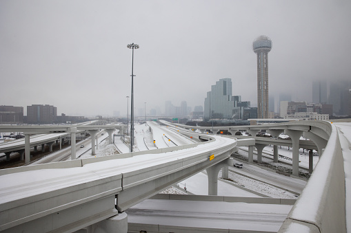 Pedestrians walk snowy streets in downtown streets during rush hour in downtown Dallas