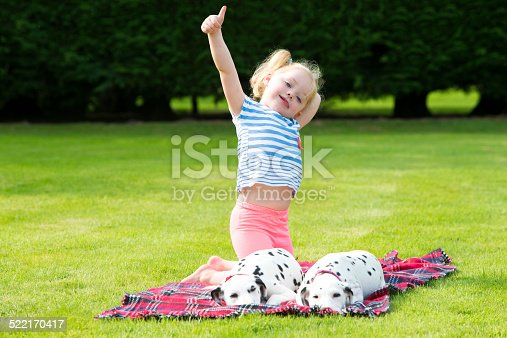 Dalmatian puppies lying on a blanket on a lawn. Little girl holds up her thumb