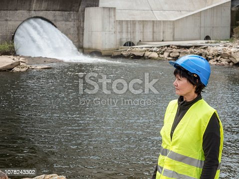 Dam and turbines of a hydroelectric power station with falling water flows and woman worker.