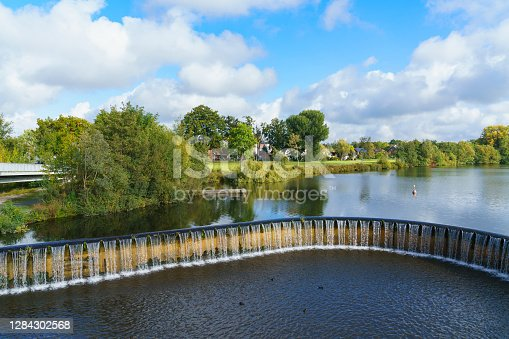 istock A dam forming a reservoir. Falling water and residential houses on the shore. 1284302568