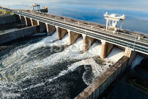 Dam with flowing water through gates. Hydroelectric power station, aerial top view.