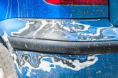 istock Damage on blue scratched car bumper with damaged and peeled paint in crash accident or parking lot 954191198