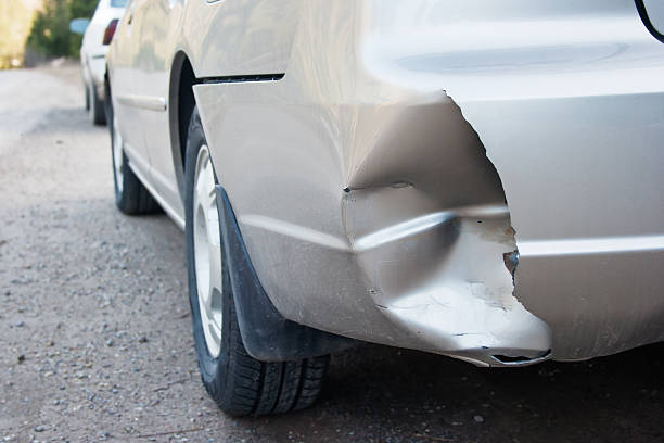 Damage Damage on the rear bumper of a car after a car accident. bumper stock pictures, royalty-free photos & images