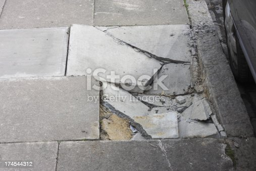 Damage to a London pavement next to the kerb. Broken paving stones in jigsaw pieces.