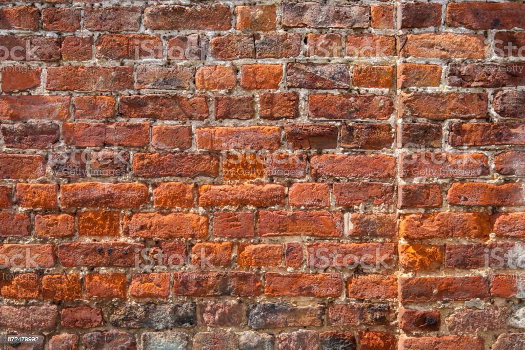 Damaged and badly repaired red brick wall full frame stock photo
