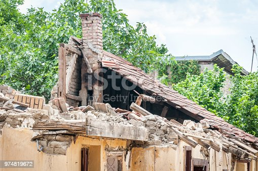 istock Damaged and broken collapsed roof of the abandoned house after fire from grenade bomb with tiles and moody sky background 974819672