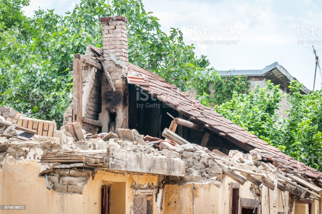 Damaged and broken collapsed roof of the abandoned house after fire from grenade bomb with tiles and moody sky background stock photo