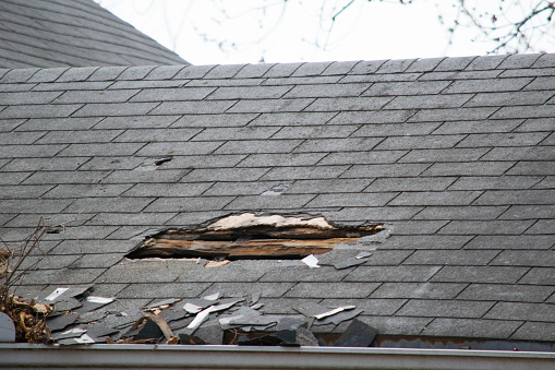 Roof of a residential house showing damage, multiple layers of shingles, missing shingles