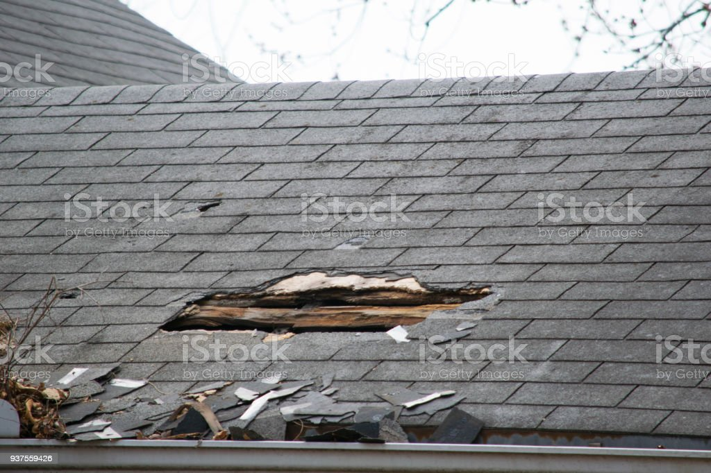 Damaged and old roofing shingles on a house stock photo