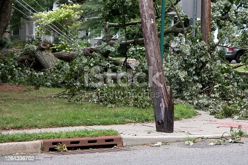 A broken utility pole downed power cable and debris after a hurricane or strong storm passed through town.