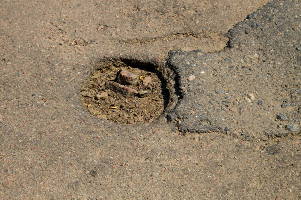 damaged asphalt road with pothole - defection stock photos and pictures