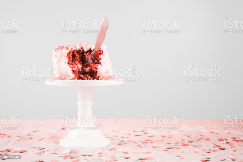 Damaged birthday cake with spoon. Birthday party celebration and messthetics concept . Living coral theme - color of the year 2019 stock photo