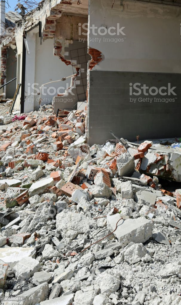 damaged building with broken walls and many bricks on the ground