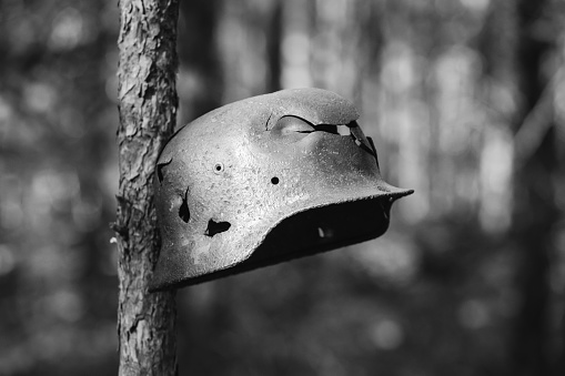 Damaged By Bullets And Shrapnel Metal Helmet Of German Infantry Wehrmacht Soldier At World War II. Rusty Helmet Hanging On Tree Trunk. Photo In Black And White Colors