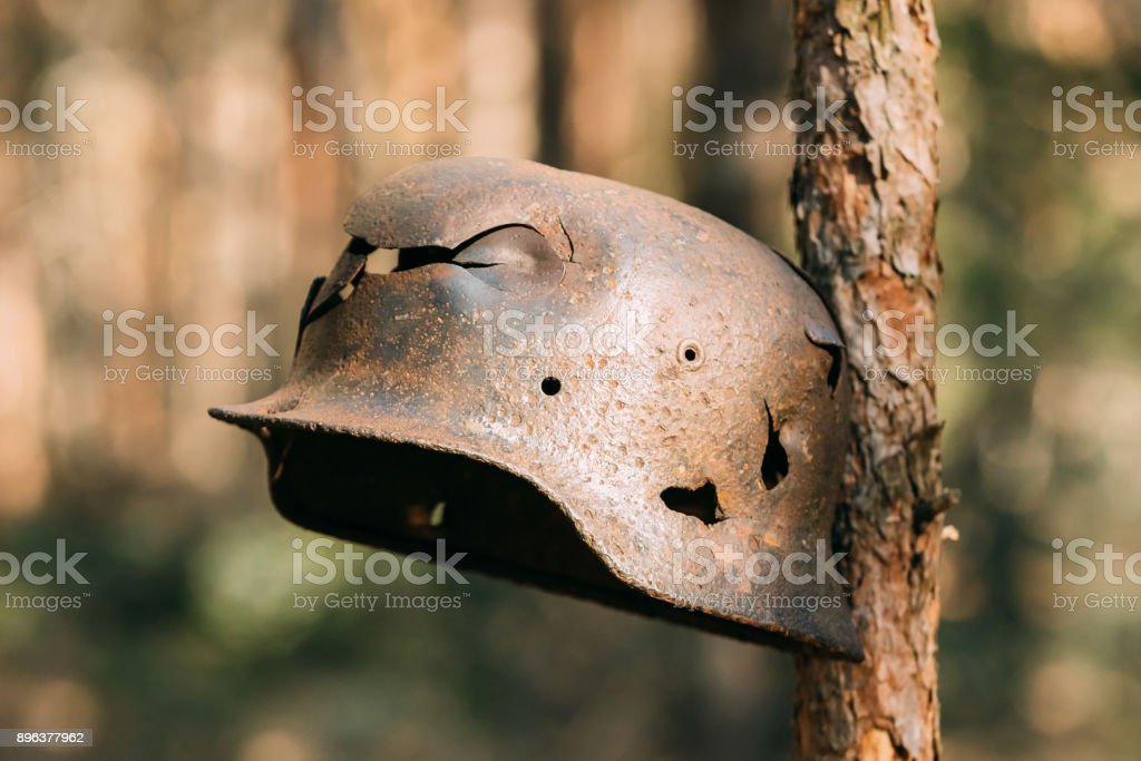Damaged By Bullets And Shrapnel Metal Helmet Of German Infantry Soldier At World War II. Rusty Helmet Hanging On Tree Trunk stock photo