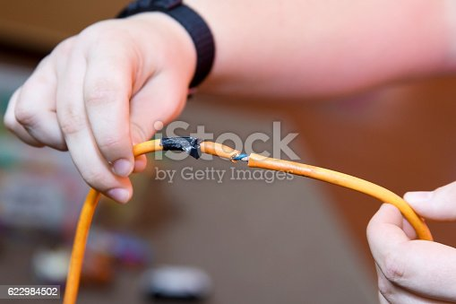 Electrician holding Portable appliance (PAT) test failure due to damaged cable. Badly repaired.
