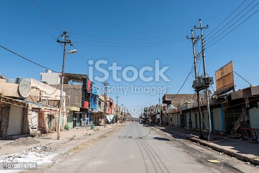Qaraqosh, Iraq - May 20, 2017: A street runs between damaged shops and other buildings in Qaraqosh, Iraq, a mostly Christian city near Mosul that was occupied and ravaged by ISIS from 2014 to 2016.