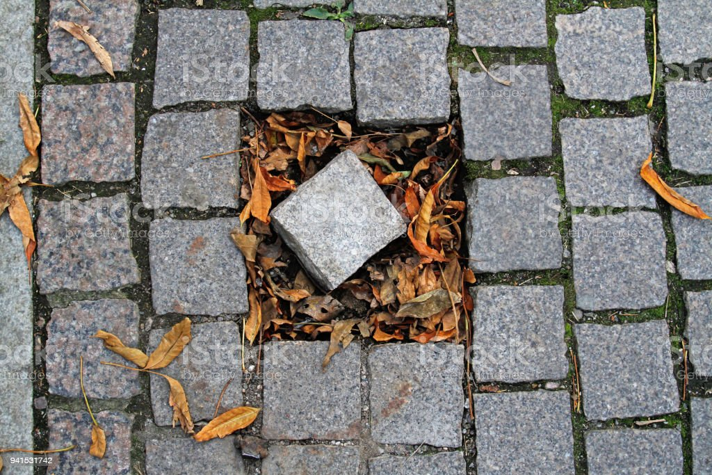Damaged cobblestone pavement with with a broken out piece, lying in...