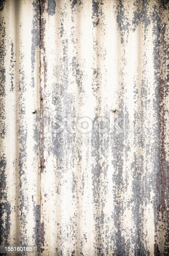 Vertical close-up of the rusty and worn corrugated metal surface of a building exterior.