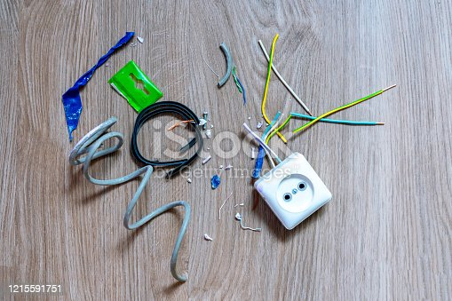 istock Damaged electrical socket with pieces of colorful wires, adhesive tape and other things on the wooden floor. Electric installation or repair work concept, indoors. 1215591751