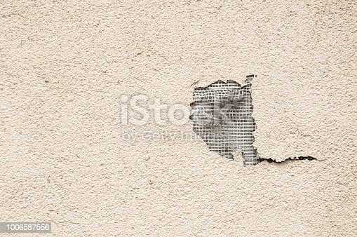 istock Damaged facade of the house or building with cracked plaster and hole in the exterior wall 1006587556