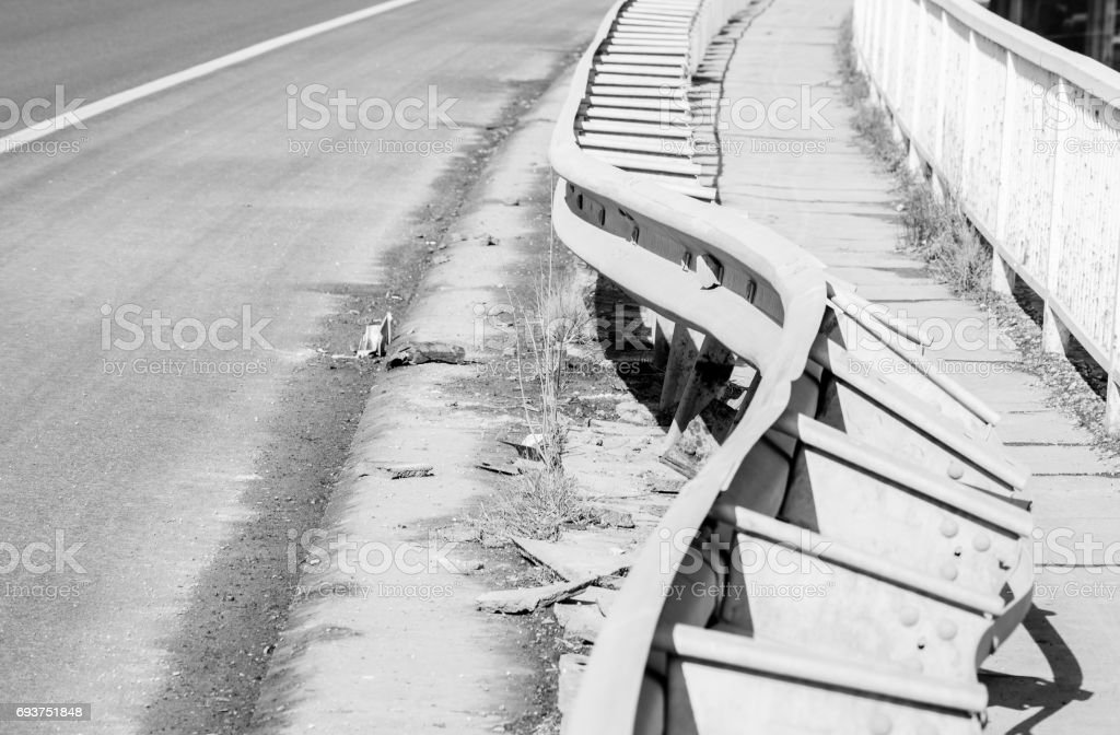 Damaged fence on the bridge from car crash accident. Selective focus. Damaged bridge. Black and white. stock photo