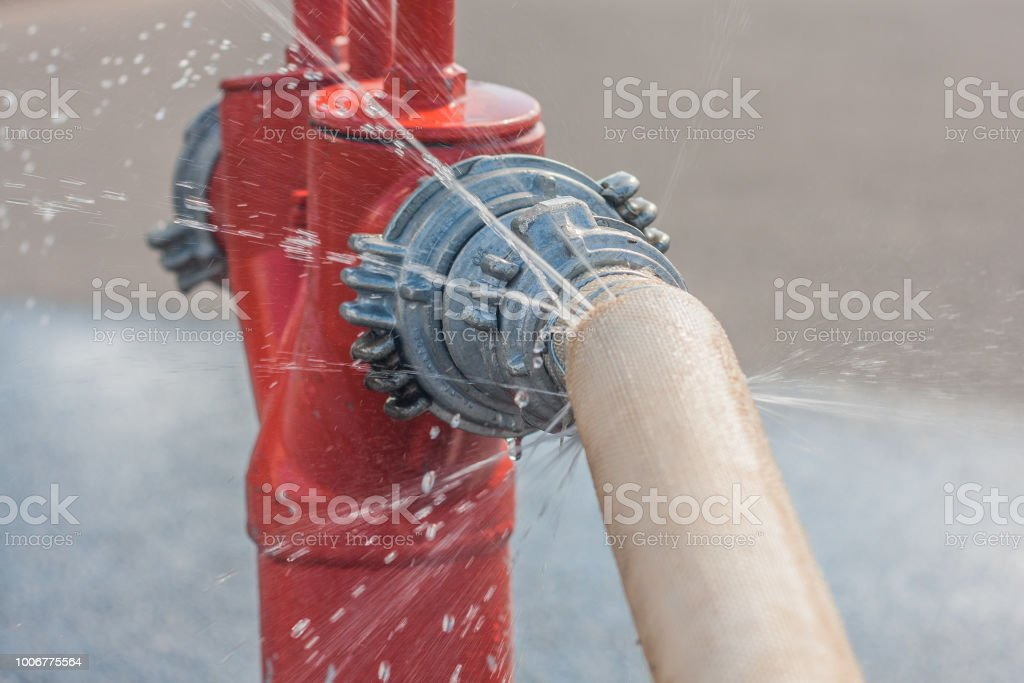 Damaged fire hose from a fire hydrant - water spray stock photo