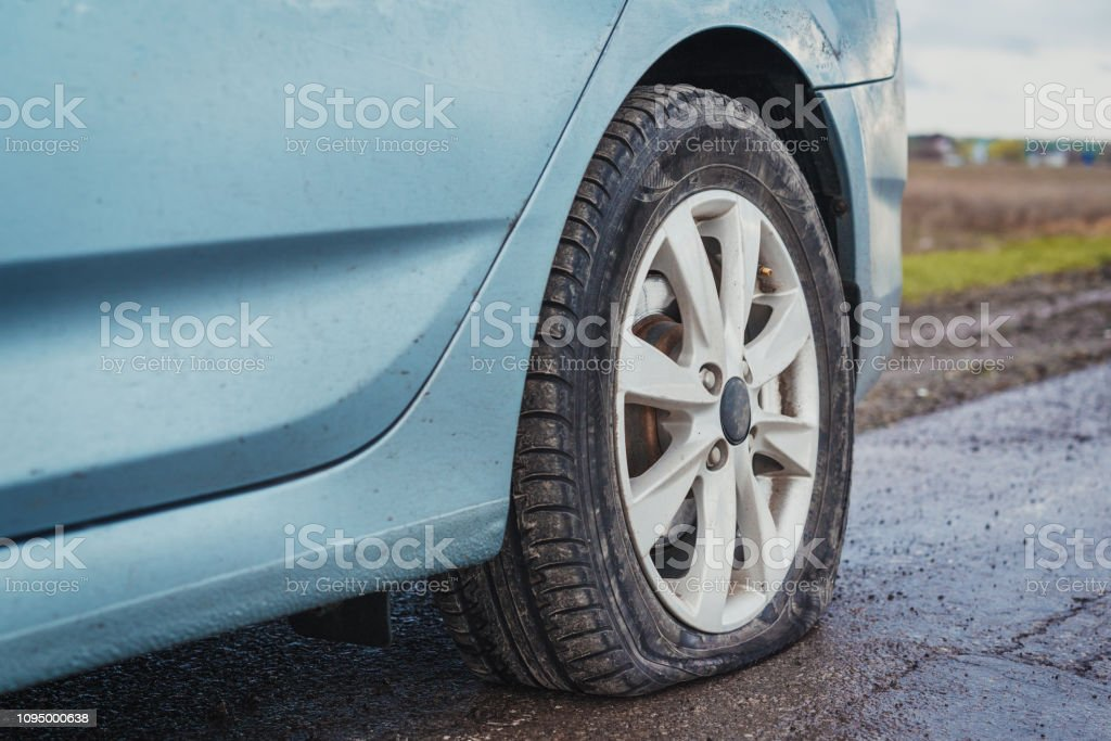 Damaged flat tire of an car on the road stock photo